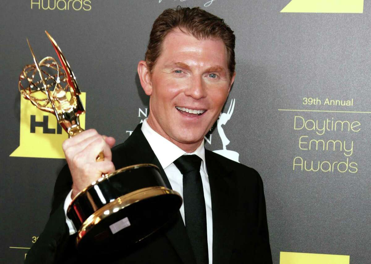 Bobby Flay poses backstage with the culinary program award for