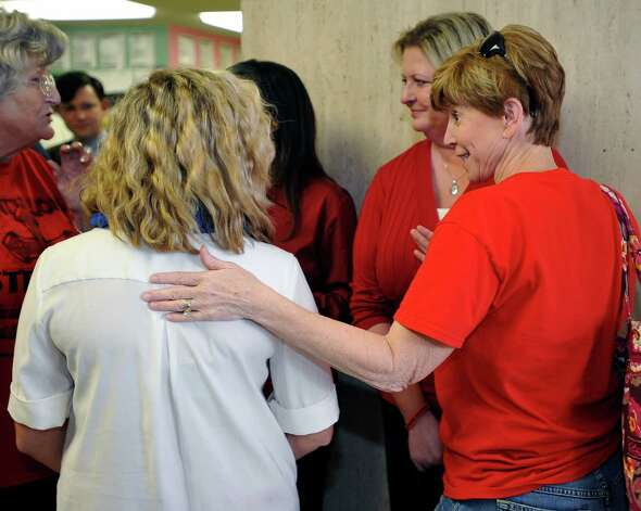 Susan Read, right, congratulates cheerleader Rebekah Richardson, left, who had just finished addressing the media and was having a chance to catch her breath.  Attorneys were back in the 356 District Court Thursday morning before Judge Steve Thomas. After hearing more arguments before lunch, Thomas announced after lunch that he would grant the temporary injunction till the jury trial date of June 24, 2013.   The Kountze cheerleaders extended temporary restraining order was due to expire Thursday at midnight. Dave Ryan/The Enterprise