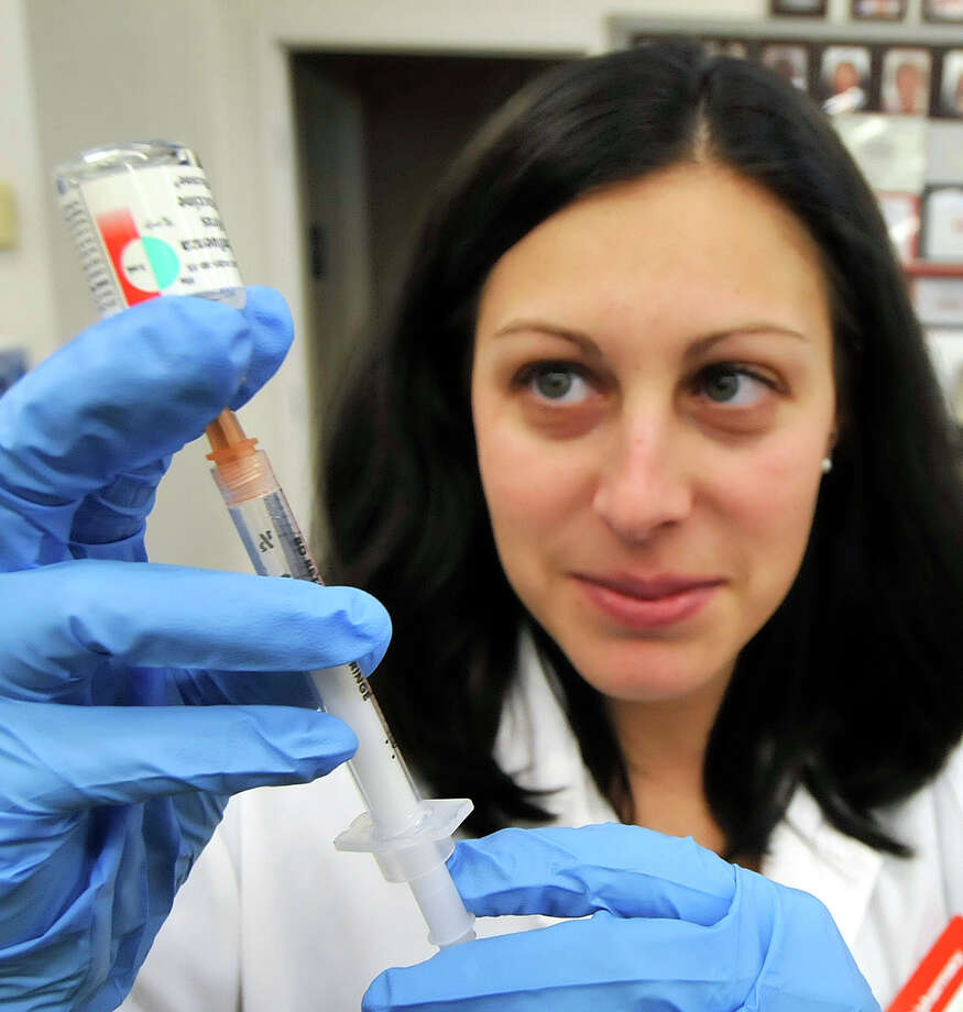 A pharmacist prepares a flu inoculation. The CDC recommends a yearly flu vaccine for everyone 6 months and older. Photo: Aonny Hedgecock / High Point Enterprise