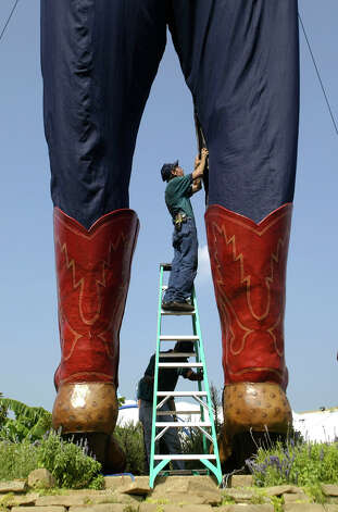 Tim Thibodeaux (top) and Charles Roberts zip up Big Tex, a 52-foot-tall talking cowboy figure before the opening of the State Fair of Texas, Tuesday, Sept. 27, 2005, in Dallas. Photo: Matt Slocum, Associated Press / AP