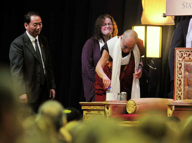 "The Dalai Lama insists on putting the cap back on the water bottle he drank from before leaving the stage at the O'Neill Center on Western Connecticut State University's westside campus in Danbury on Friday, Oct. 19, 2012. The Dalai Lama gave his speach, ""Advice for Daily Life,"" before answering questions. Photo: Jason Rearick / The News-Times"