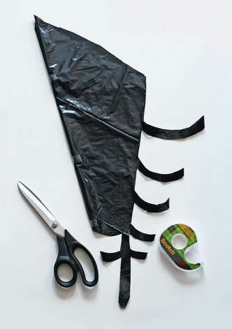 A large plastic garbage bag, a pair of scissors and tape are all you need to make spider webs. Photo: Jessica Jones