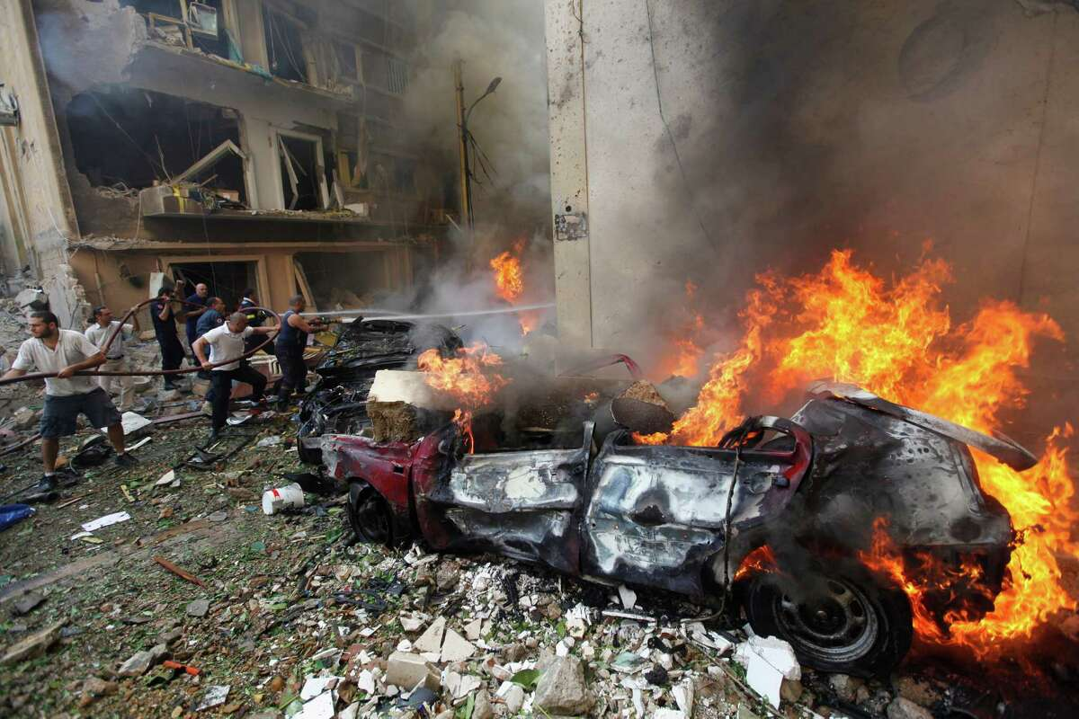 Lebanese firefighters extinguish burning cars at the scene of an explosion in the mostly Christian neighborhood of Achrafiyeh, Beirut, Lebanon, Friday Oct. 19, 2012. Lebanon's state-run news agency says a massive blast in east Beirut was caused by a car bomb and that there are casualties. An Associated Press reporter at the scene saw bloodied people being helped into ambulances and heavy damage to what appeared to be residential buildings.