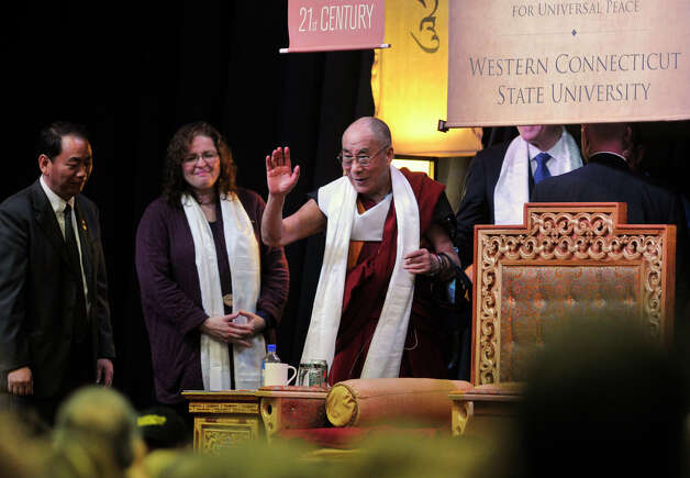 "The Dalai Lama, center, waves to spectators after giving his ""Advice for Daily Life"" speech in the O'Neill Center on Western Connecticut State University's westside campus in Danbury on Friday, Oct. 19, 2012. Photo: Jason Rearick / The News-Times"