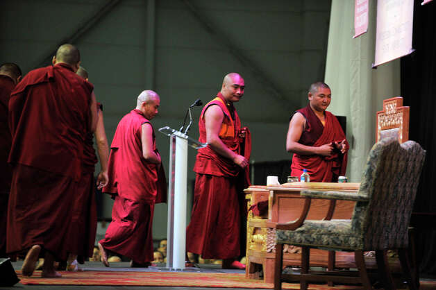 After chanting, the Buddhist monks leave the stage, passing the Dalai Lama's chair in the O'Neill Center on Western Connecticut State University's westside campus in Danbury on Friday, Oct. 19, 2012. Photo: Jason Rearick / The News-Times