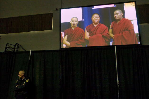 Security personnel stand next to the stage as Buddhist monks chant before the Dalai Lama's arrival on the O'Neill Center stage on Western Connecticut State University's westside campus in Danbury on Friday, Oct. 19, 2012. Photo: Jason Rearick / The News-Times