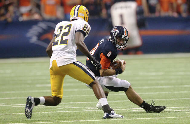 UTSA's Eric Soza (08) scrambles from Texas A&M-Commerce's Shaquelle Massey (22) at the Alamodome on Saturday, Sept. 8, 2012. The Roadrunners defeated the Lions, 27-16. Over 30,000 were in attendance. Photo: Kin Man Hui, SAN ANTONIO EXPRESS-NEWS / ©2012 San Antonio Express-News