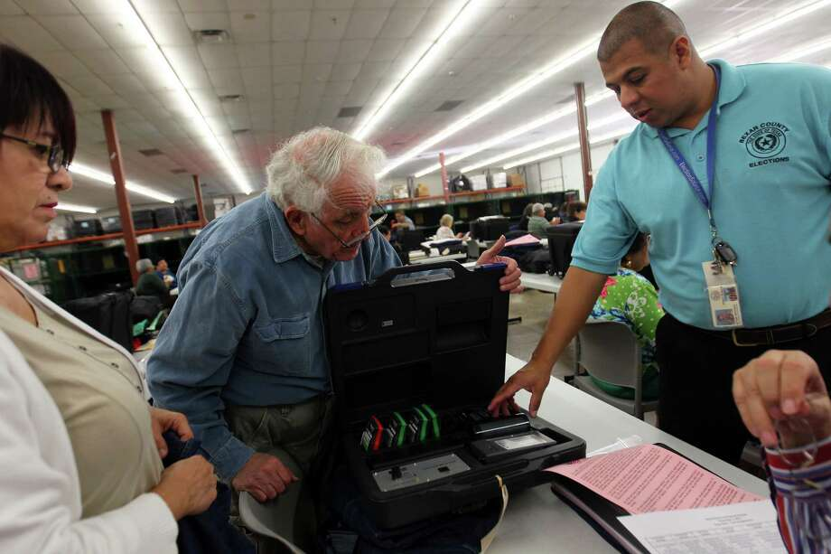 Sylvia Pena (from left) and Stanley Steger verify the contents of their equipment case with the help of technical support team member Antonio Maradiagas at the Bexar County Elections Warehouse. Early voting will begin Monday. Photo: Jennifer Whitney, For The Express-News / © Jennifer Whitney