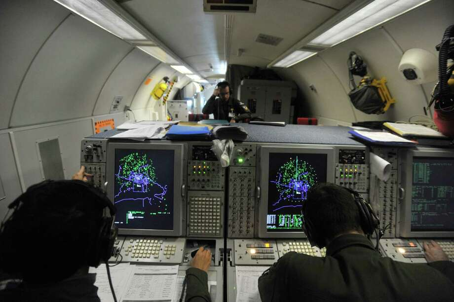 Crew members work aboard a French E-3 during an air surveillance mission above the Mediterranean sea on March 23, 