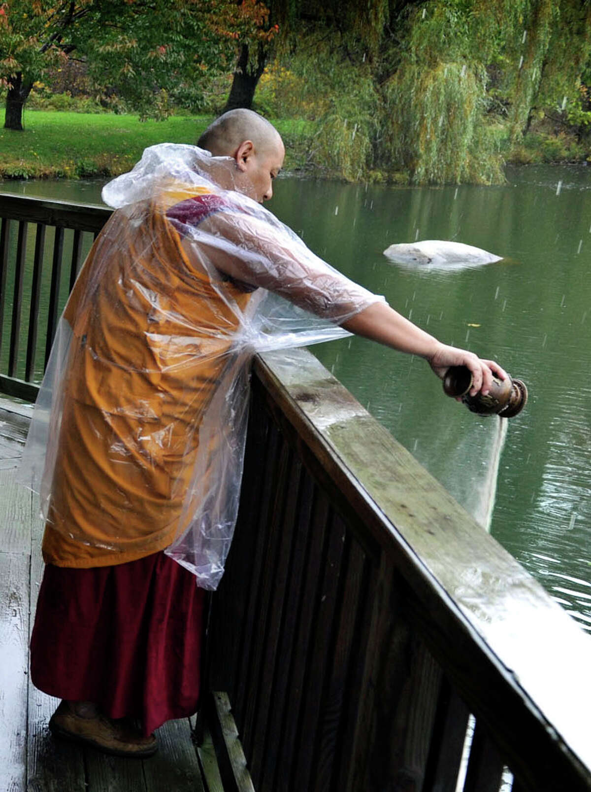 Tibetan Buddhist monks perform a ceremony in which after dissolving the sand mandala that they created in honor of the visit of the Dalai Lama to Danbury, they pour the sand into a pond at the Ives Concert Park, Friday, Oct. 19, 2012.