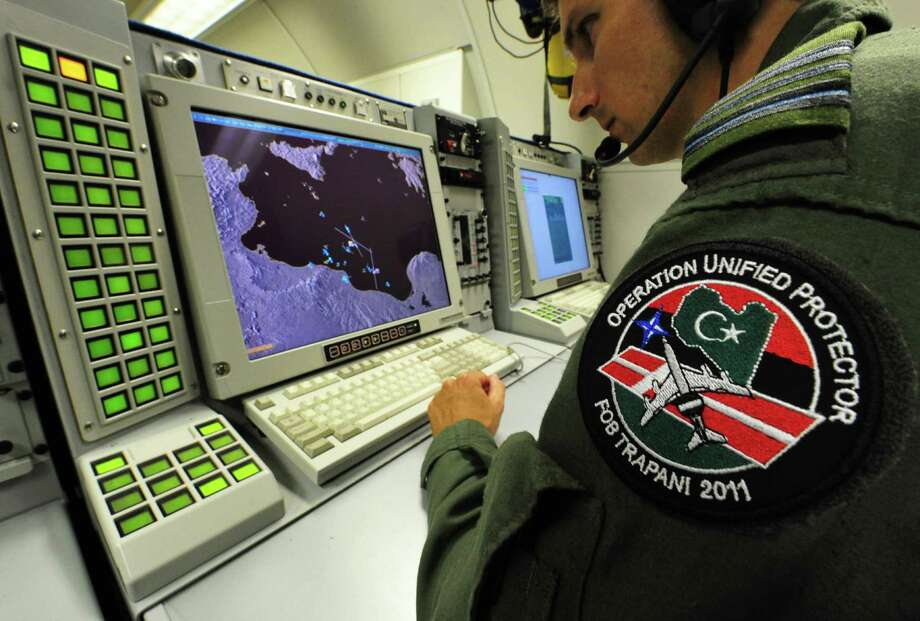 A crew member works inside a NATO E-3 AWACS aircraft on July 9, 2011 while flying over the Mediterranean sea during the NATO Unified Protector operation over Libya. Photo: ALBERTO PIZZOLI, AFP/Getty Images / 2011 AFP