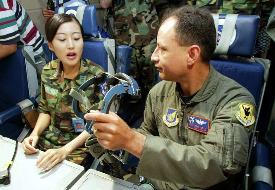 A U.S. Air Force soldier talks with a South Korean soldier about the equipment in an E-3 Sentry AWACS jet at the U.S. Air Force base June 12, 2003 in Osan, South Korea. Photo: Chung Sung-Jun, Getty Images / 2003 Getty Images
