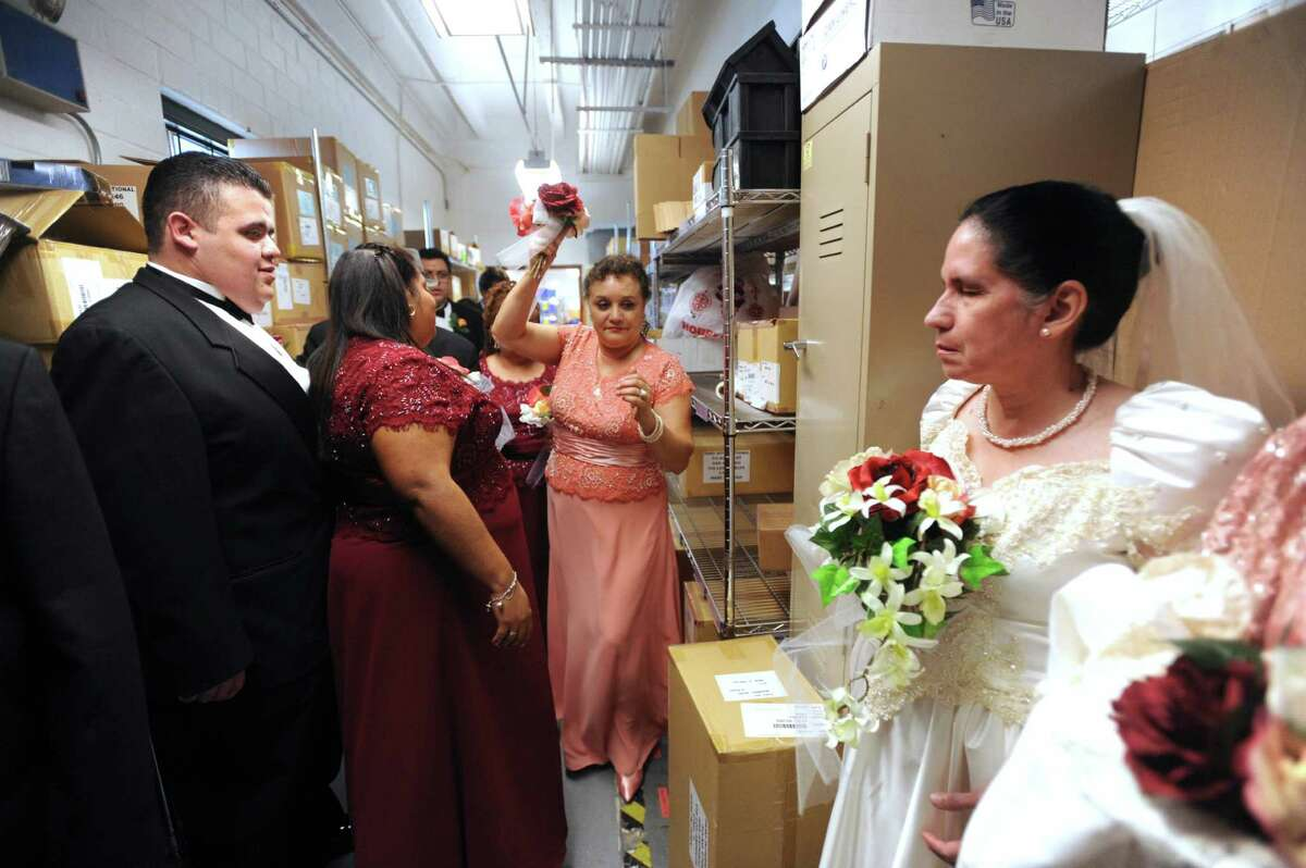 Linda Saenz brings more flowers to bride Velia Estrada, right, before her wedding to Jesse Talamantes at the San Antonio Lighthouse for the Blind on Friday, Oct. 19, 2012. The wedding was the first in the facility's 79-year history.