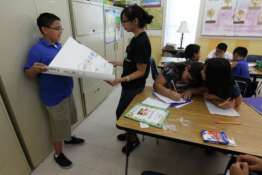 Sixth-grader Jonathan Alvarado (left) shows his work  on planets  to tutor Veronica Fuentes at American Sunrise Learning Center. The after-school program caters to children from kindergarten through  12th grade. Photo: Kin Man Hui, San Antonio Express-News / ©2012 San Antonio Express-News
