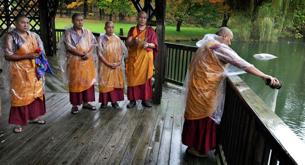 Tibetan Buddhist monks perform a ceremony in which after dissolving the sand mandala that they created in honor of the visit of the Dalai Lama to Danbury, they pour the sand into a pond at the Ives Concert Park, Friday, Oct. 19, 2012. Photo: Carol Kaliff / The News-Times