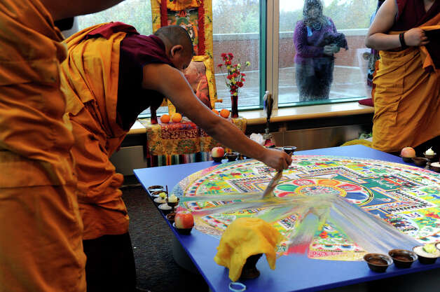 Tibetan Buddhist monks begin the dissolving process of a sand mandala that they created in honor of the visit of the Dalai Lama to Danbury, Friday, Oct. 19, 2012. Photo: Carol Kaliff / The News-Times