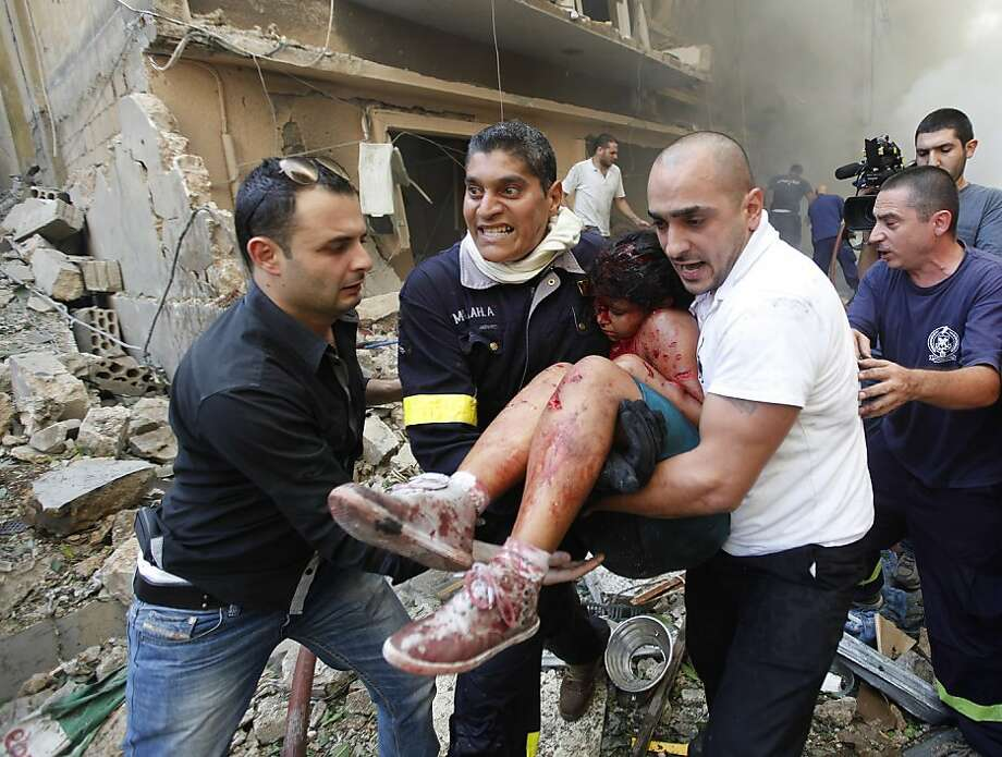 Lebanese rescue workers and civilians carry an injured girl from the scene of an explosion in the mostly Christian neighborhood of Achrafieh, Beirut. Photo: Hussein Malla, Associated Press