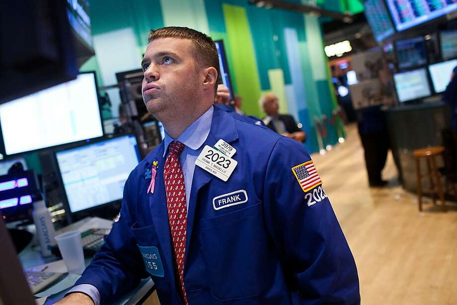 A trader works the floor of the New York Stock Exchange, where declines left major indexes clinging to the week's gains. Photo: Andrew Burton, Getty Images