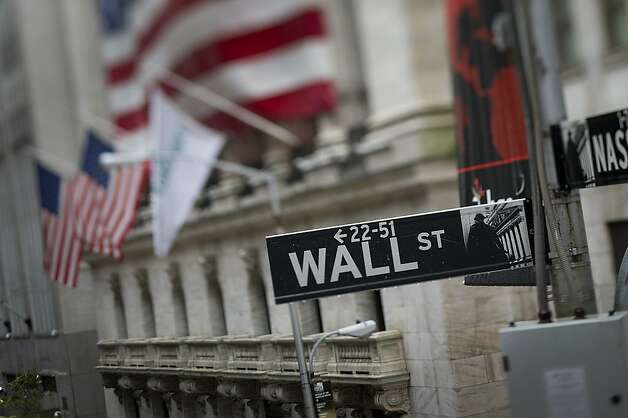 A sign for Wall St. is displayed in front of the New York Stock Exchange (NYSE) stands in this photo taken with a tilt-shift lens in New York, U.S., on Friday, Oct. 19, 2012. U.S. stocks fell, trimming the biggest weekly advance for the Standard & Poor's 500 Index in a month, as Microsoft Corp. and General Electric Co. (GE) posted sales that missed estimates and euro-area leaders agreed on a banking regulation timetable. Photographer: Scott Eells/Bloomberg Photo: Scott Eells, Bloomberg