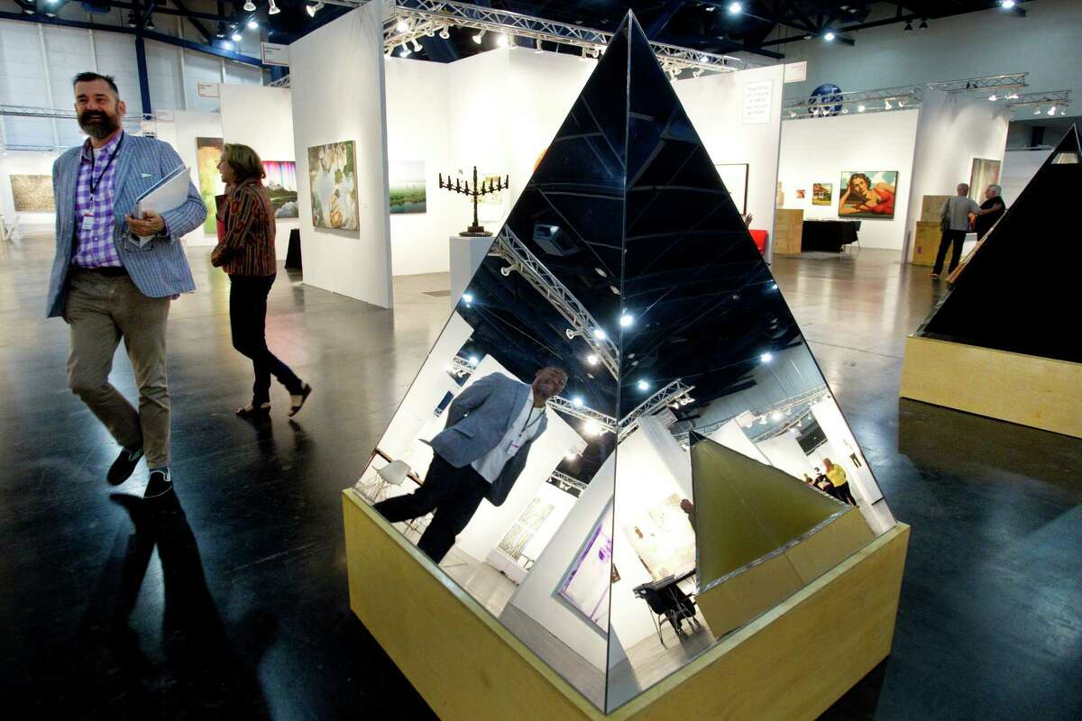 Bill Arning, director of the Contemporary Arts Museum Houston, left, and Franklin Sirmans, reflected, chief curator of the Los Angeles County Museum of Art, walk past Agnes Denes' Pyramids of Conscience at the Texas Contemporary Art Fair at the George R. Brown Convention Center Friday, Oct. 19, 2012, in Houston.