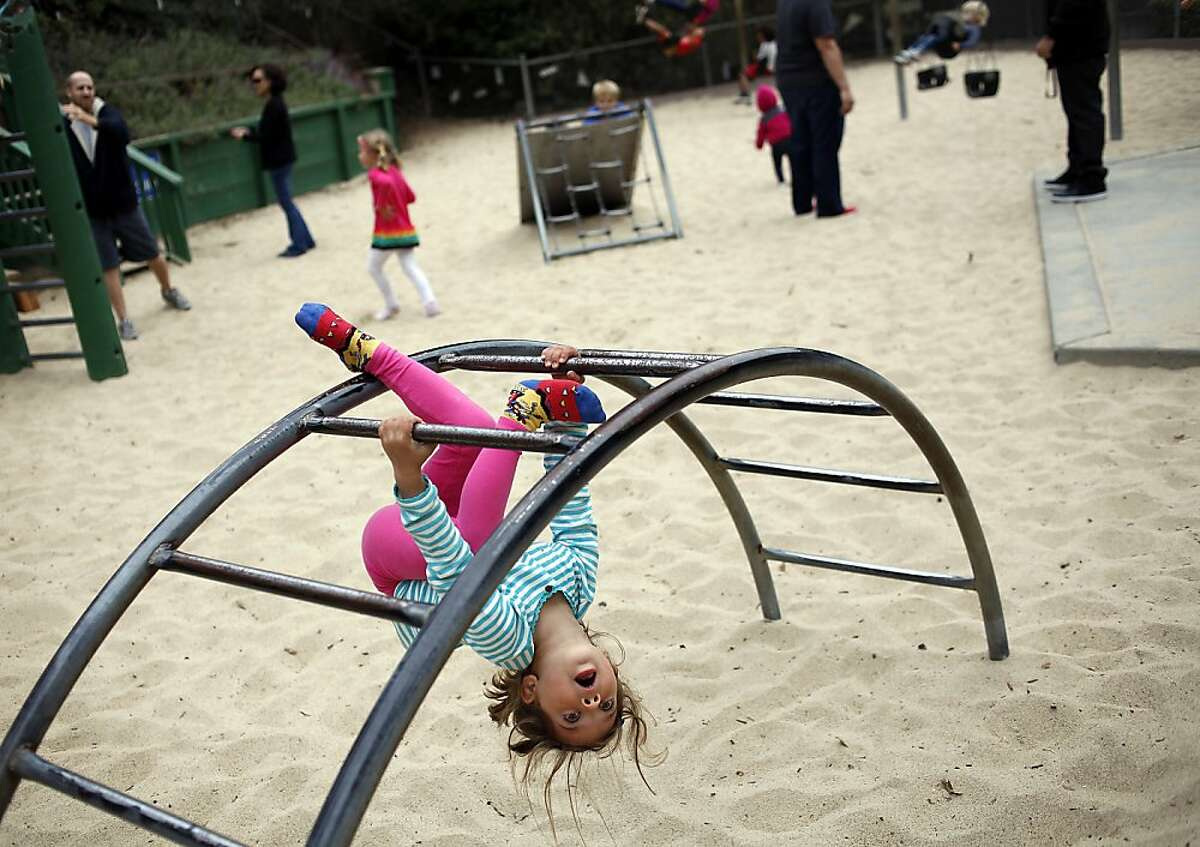 Elizabeth Hasse, 4, of San Francisco, hangs from the bars at Glen Canyon Park in San Francisco, Calif., Friday, October 19, 2012. A renovation to the playground and recreation center are being held up by a citizen protesting the removal of trees. Fifty-eight trees are slated to be removed and replaced with 163 new trees.