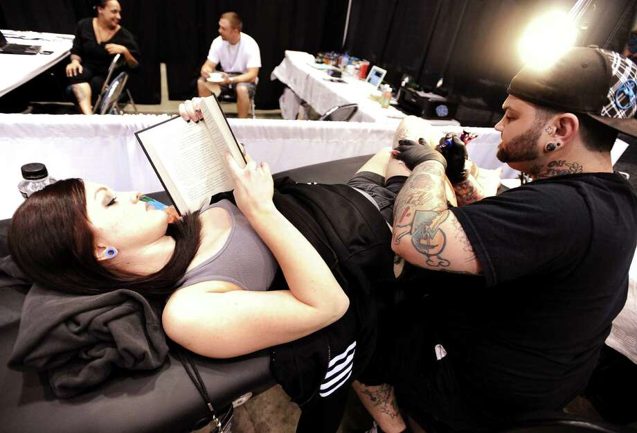 Sarah Leger is being tattooed by Tony Wayne of the Imperial Tattoo Company based in Sugarland at the Immersed In Ink Tattoo & Arts Festival at the Beaumont Civic Center on Friday, October 19, 2012. Photo taken: Randy Edwards/The Enterprise Photo: Randy Edwards