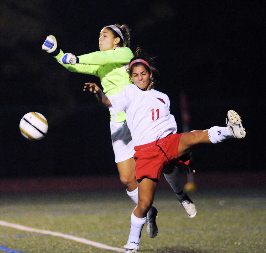 Darien goalie Phoebe Taylor blocks a shot as Kim Ghahramani # 11 of Greenwich misses while attempting a header on the rebound during the closing minute of play in the first half during the girls high school soccer match between Greenwich High School and Darien High School at Greenwich, Friday night, Oct. 19, 2012. The game ended in a scoreless tie. Photo: Bob Luckey / Greenwich Time