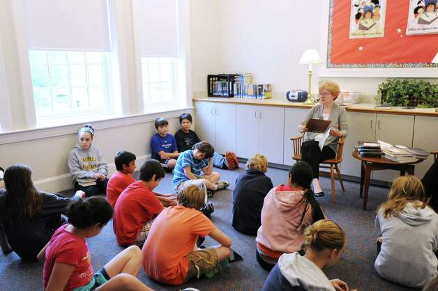Children's Librarian Kathy Jarombek, right, of Greenwich, leads a young critics reading group at the Perrot Memorial Library where she works in Old Greenwich, Friday afternoon, Oct. 19, 2012. Jarombek was appointed to the selection committee for the prestigious Newbery Medal that is given annually by the Association for Library Service to Children to a selected author for distinguished contribution to American literature. Photo: Bob Luckey / Greenwich Time
