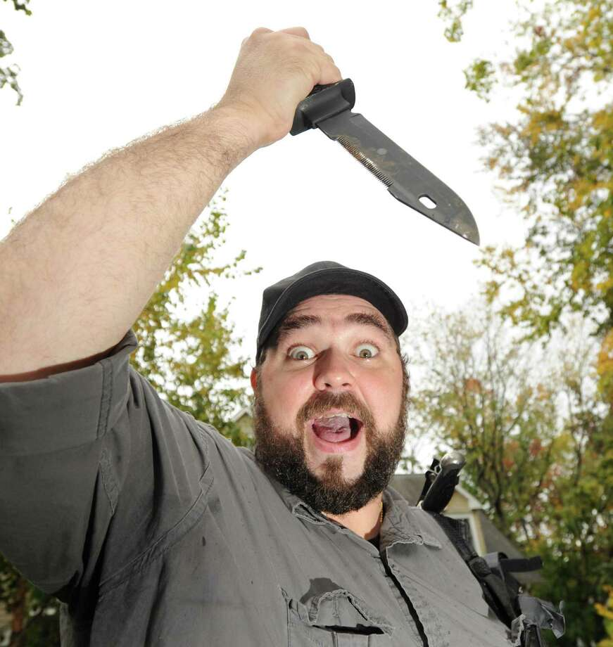 "Director Thomas Ascenzi of Greenwich screams as he strikes a pose with a prop-knife from his upcoming horror-thriller film ""The House Sitter,"" at the Riverside home where Ascenzi said most of the movie was shot, Friday afternoon, Oct. 19, 2012. Photo: Bob Luckey / Greenwich Time"