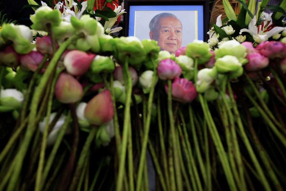 A portrait of King Norodom Sihanouk is embedded among flower offerings by mourners for his death at the Royal Palace in Phnom Penh, Cambodia, Tuesday, Oct. 16, 2012. Sihanouk died Monday at age 89 of a heart attack in Beijing, where he had been receiving medical treatment since January for multiple ailments. Photo: Wong Maye-E, Associated Press / AP