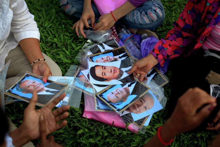 People sort out portraits of the late King Norodom Sihanouk for sale at the Royal Palace in Phnom Pe