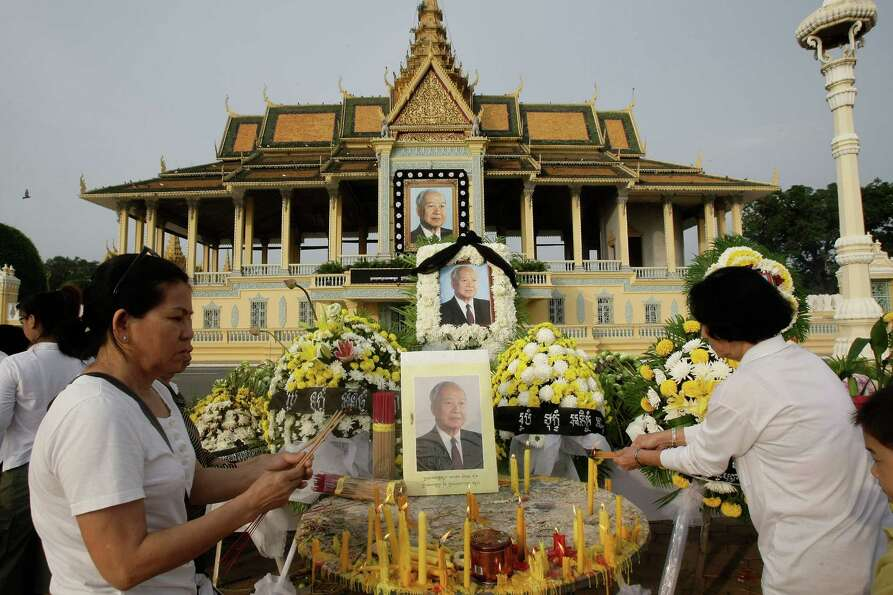 Cambodians burn incense stick as they offer prayers in front of the Royal Palace in Phnom Penh, Camb