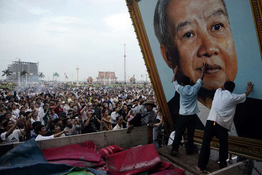 Cambodian people watch as workers install a portrait of the late former king Norodom Sihanouk in fro