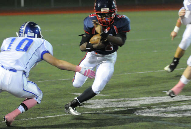 McMahon's Trevon Forney gains yards as Ludlowe's Thomas Howell moves in as Brien McMahon hosts Fairfield Ludlowe in a football game in Norwalk, Conn., Oct. 19, 2012. Photo: Keelin Daly / Stamford Advocate Freelance