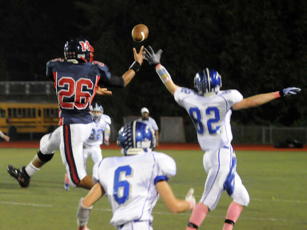 McMahon's Kenneth Keen and Ludlowe's Victor D'Ascenzo fight for the ball as Brien McMahon hosts Fairfield Ludlowe in a football game in Norwalk, Conn., Oct. 19, 2012. Photo: Keelin Daly / Stamford Advocate Freelance
