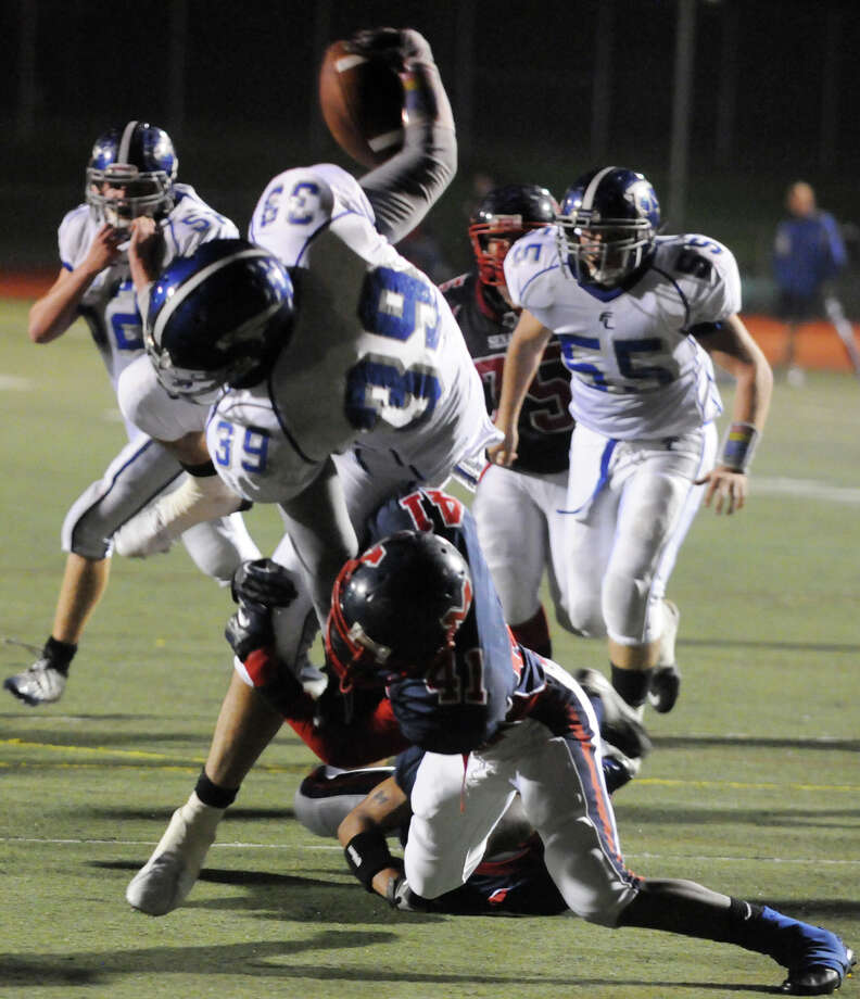 Ludlowe's Christian Ghiorzi pushes for yards as McMahon's Kentrell Snider pushes back as Brien McMahon hosts Fairfield Ludlowe in a football game in Norwalk, Conn., Oct. 19, 2012. Photo: Keelin Daly / Stamford Advocate Freelance