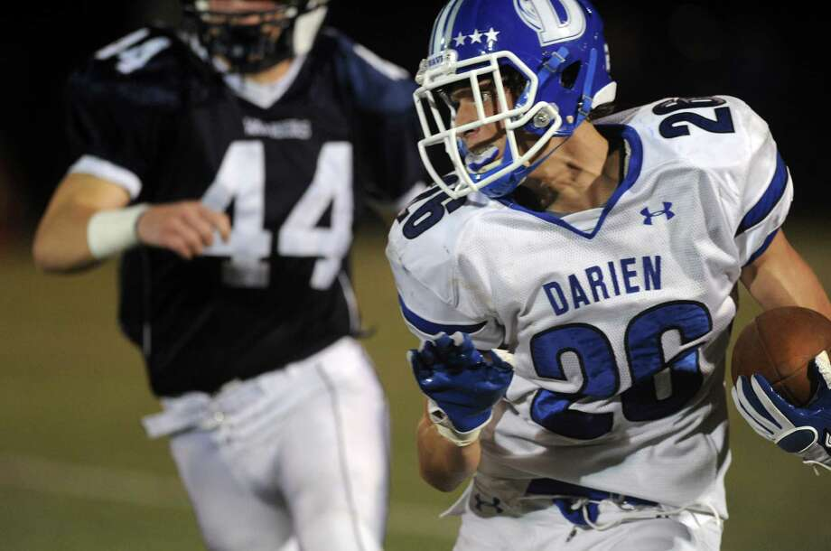 Darien's Peter Gesualdi carries the ball during Friday's football game at Wilton High School on October 19, 2012. Photo: Lindsay Niegelberg / Stamford Advocate