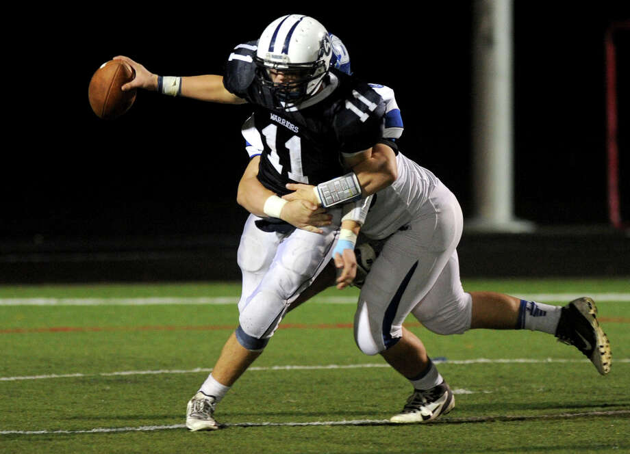 A Darien defender tackles Wilton quarterback Brett Phillips during Friday's football game at Wilton High School on October 19, 2012. Photo: Lindsay Niegelberg / Stamford Advocate