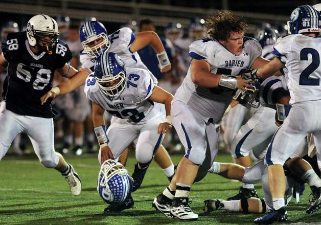 Darien's Matthew D'Andrea loses his helmet during Friday's football game at Wilton High School on October 19, 2012. Photo: Lindsay Niegelberg / Stamford Advocate