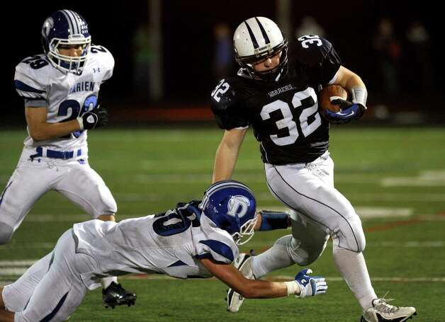 Wilton's John D'elisa evades a tackle during Friday's football game at Wilton High School on October 19, 2012. Photo: Lindsay Niegelberg / Stamford Advocate