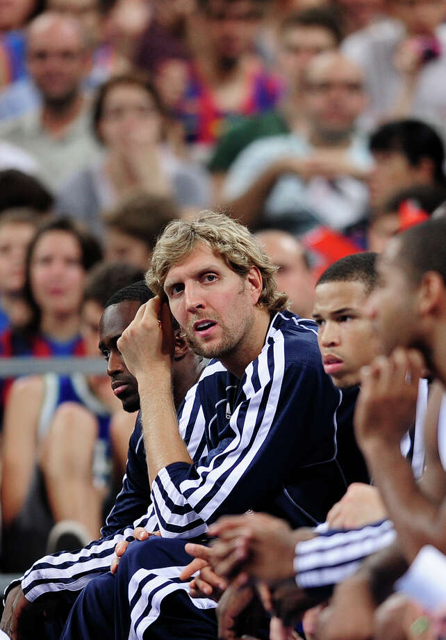 Mavericks forward Dirk Nowitzki watches a preseason game from the sidelines. His only preseason action came in the opener in his native Germany. Photo: MANU FERNANDEZ / AP