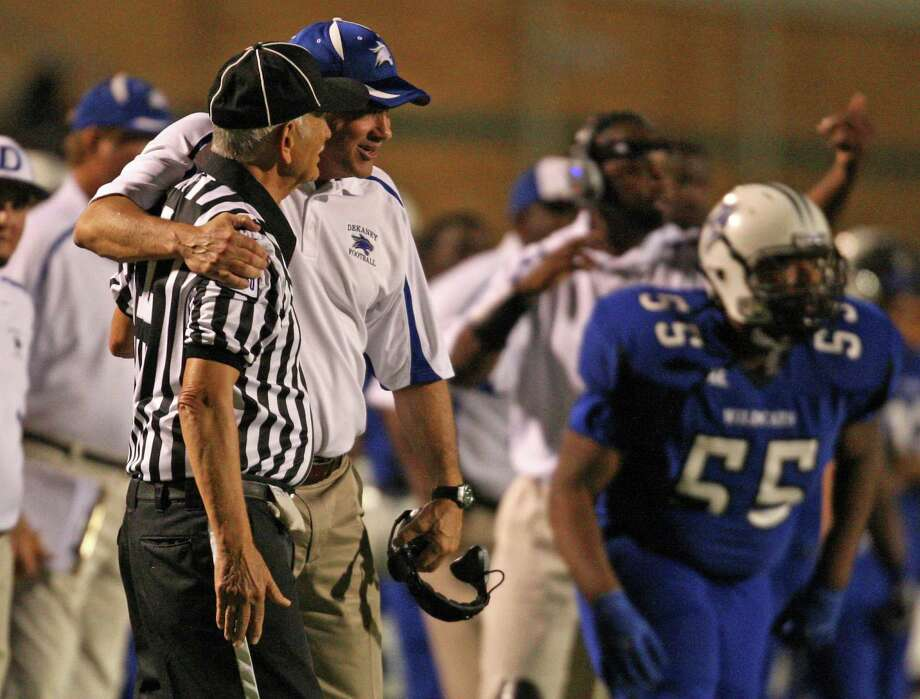 After arguing over a call, Dekaney head coach Willie Amendola hugs line judge Joseph Mechelay during the first half of a high school football game against Klein Collins, Friday, October 19, 2012 at George Stadium in Spring, TX. Photo: Eric Christian Smith, For The Chronicle