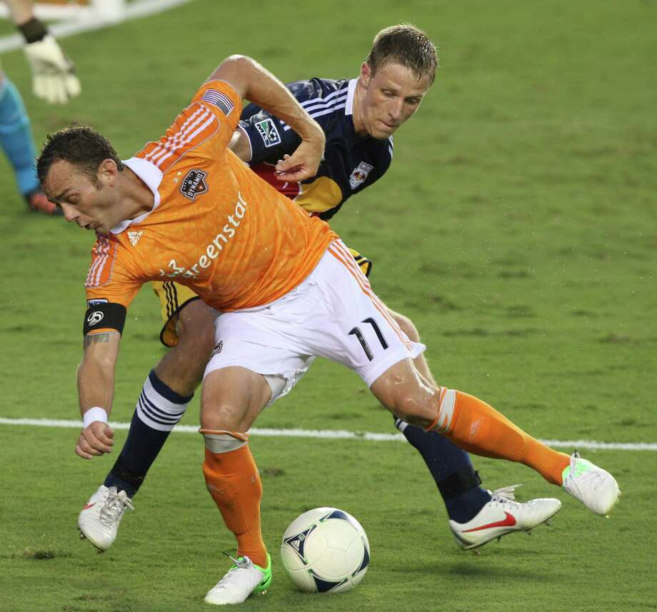 Dynamo midfielder Brad Davis, trying to elude Red Bulls midfielder Jan Gunnar Solli, will be available after being sidelined with a calf injury. Photo: J. Patric Schneider / © 2012 Houston Chronicle