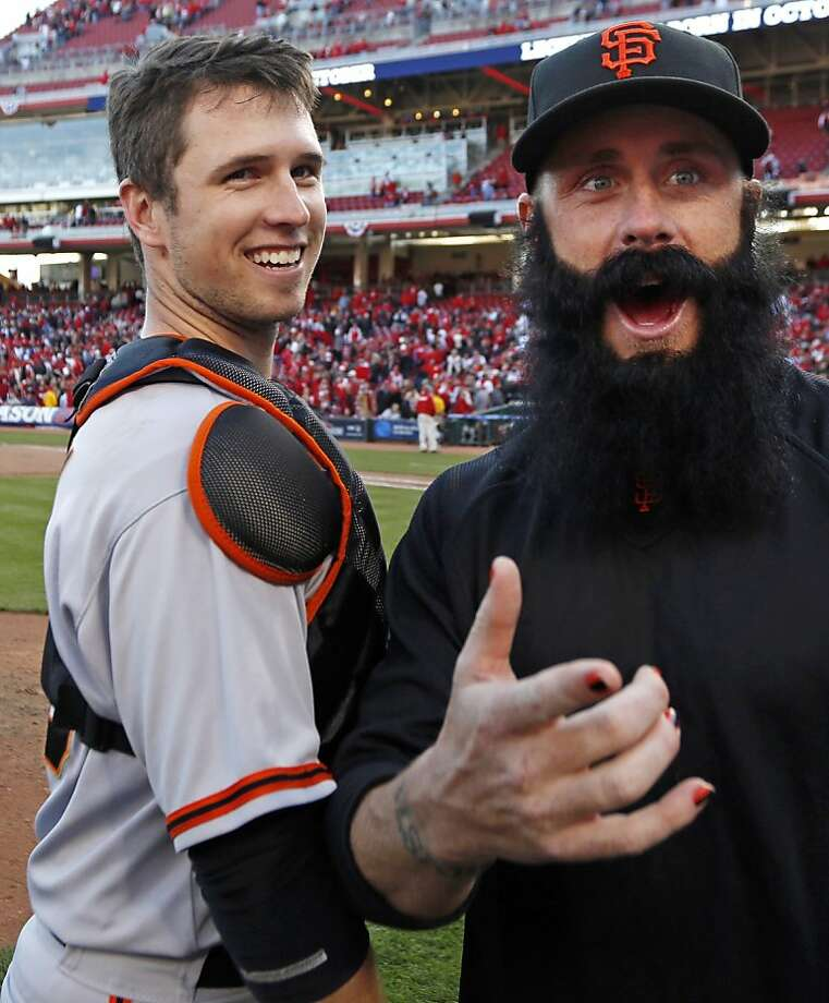 San Francisco Giants' Buster Posey celebrates with pitcher Brian Wilson after they defeated the Cincinnati Reds 6-4 in Game 5 of the National League division baseball series, Thursday, Oct. 11, 2012, in Cincinnati.  The Giants won the final three games, all in Cincinnati, and advanced to the NL championship series. (AP Photo/David Kohl) Photo: David Kohl, Associated Press