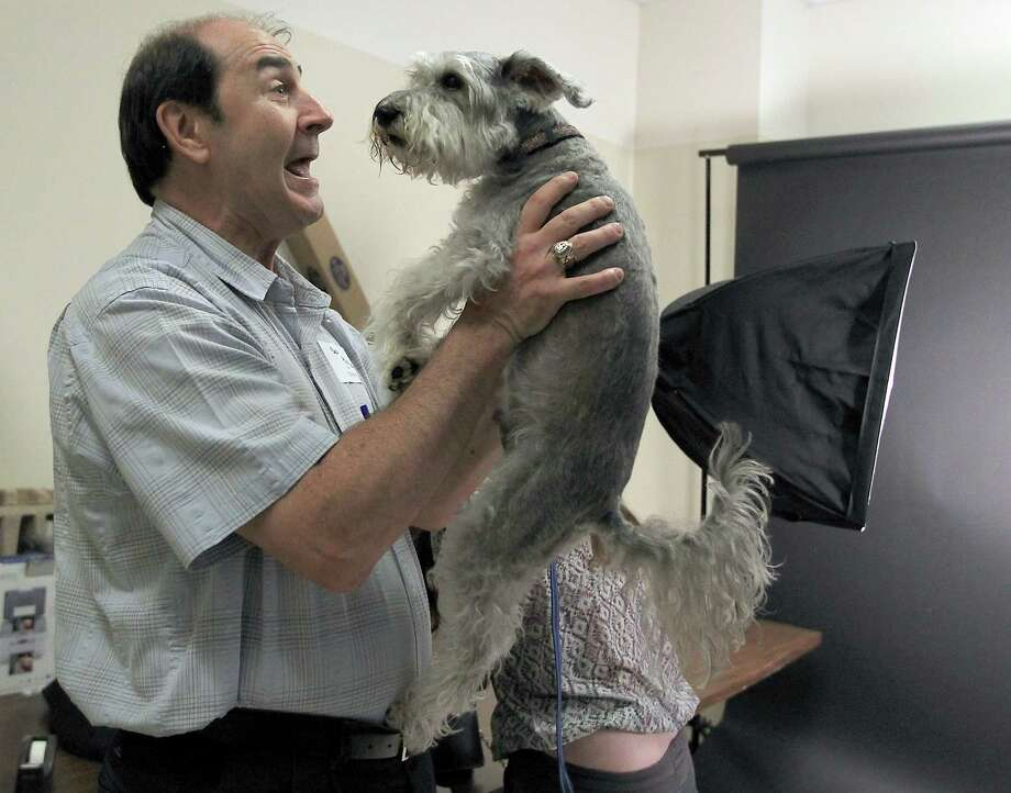 """Bob Plessala holds """"Dobie"""", who was a Pet of the Week in January 2009, after she had her photo taken by Mary Pasicatan during the reunion party for Ken Hoffman's Pethouse Pets of the Week at Citizens for Animal Protection, Friday, Oct. 19, 2012, in Houston. Hoffman started the column when he joined the Chronicle in 1995. Each week he features a CAP dog. In all the years since, every Pethouse dog featured in the Sunday Zest section has been adopted. Photo: Karen Warren, Houston Chronicle / © 2012  Houston Chronicle"""