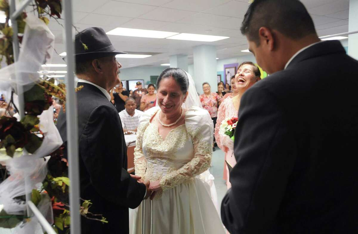 Jesse Talamantes and Velia Estrada smile as Pastor Robert Flores speaks about love during their wedding ceremony at the San Antonio Lighthouse for the Blind on Friday, Oct. 19, 2012. Talamantes, who has only partial peripheral vision in one eye, can often be found leading and caring for Estrada, who is completely blind.