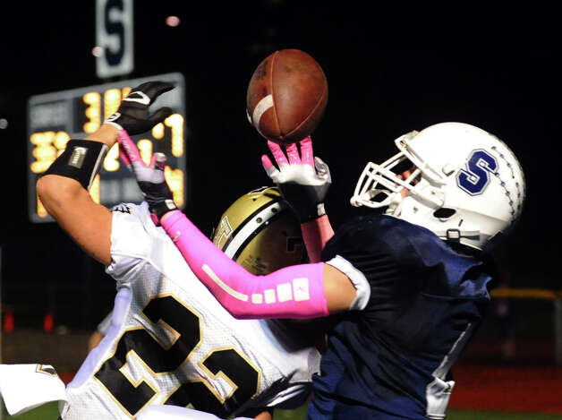 Staples' #4 James Frusciante, right, goes to grab a touchdown pass, during football action against Trumbull in Westport, Conn. on Friday October 19, 2012. Photo: Christian Abraham / Connecticut Post