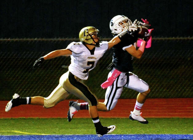 Staples' #4 James Frusciante, right, completes a touchdown pass as Trumbull's #7 Thomas Hayduk tries to disrupt it, during football action in Westport, Conn. on Friday October 19, 2012. Photo: Christian Abraham / Connecticut Post