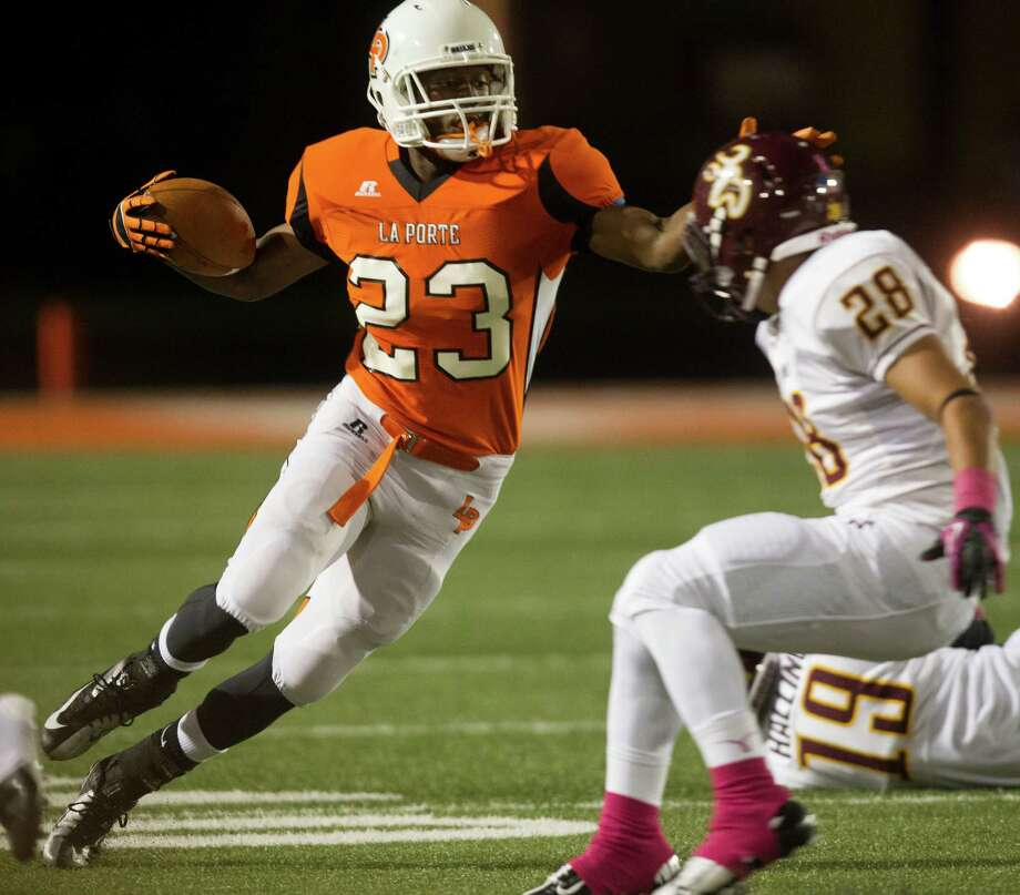 La Porte running back Johnathan Lewis (23) runs for extra yards against Deer Parks's Eric Benavidez (28) during the second quarter of a high school football game at Bulldog Stadium on Friday, Oct. 19, 2012, in La Porte. Photo: J. Patric Schneider, For The Chronicle / © 2012 Houston Chronicle