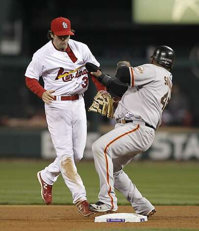 Cardinals' Pete Kozma and Giants' Pablo Sandoval get tangled up on a throw to second base  during a single by Hunter Pence that scored Marco Scutaro in the fourth inning, as the San Francisco Giants take on the St. Louis Cardinals in game five of the National League Championship Series, on Friday Oct. 19, 2012 at Busch Stadium , in  St. Louis, Mo. Photo: Michael Macor, The Chronicle